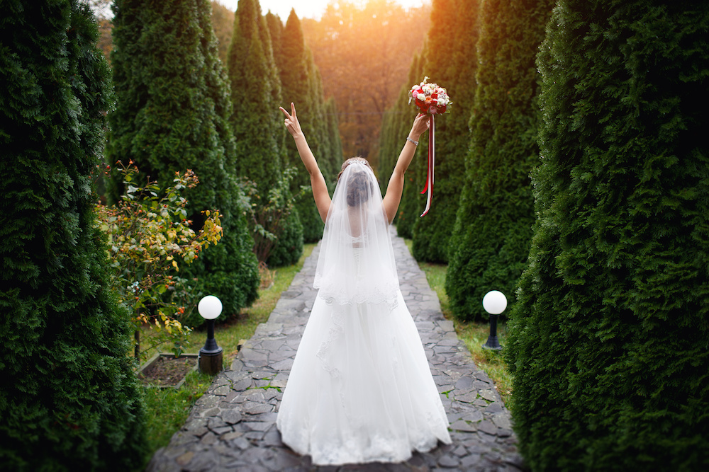 wedding bride with flowers amidst cypress trees