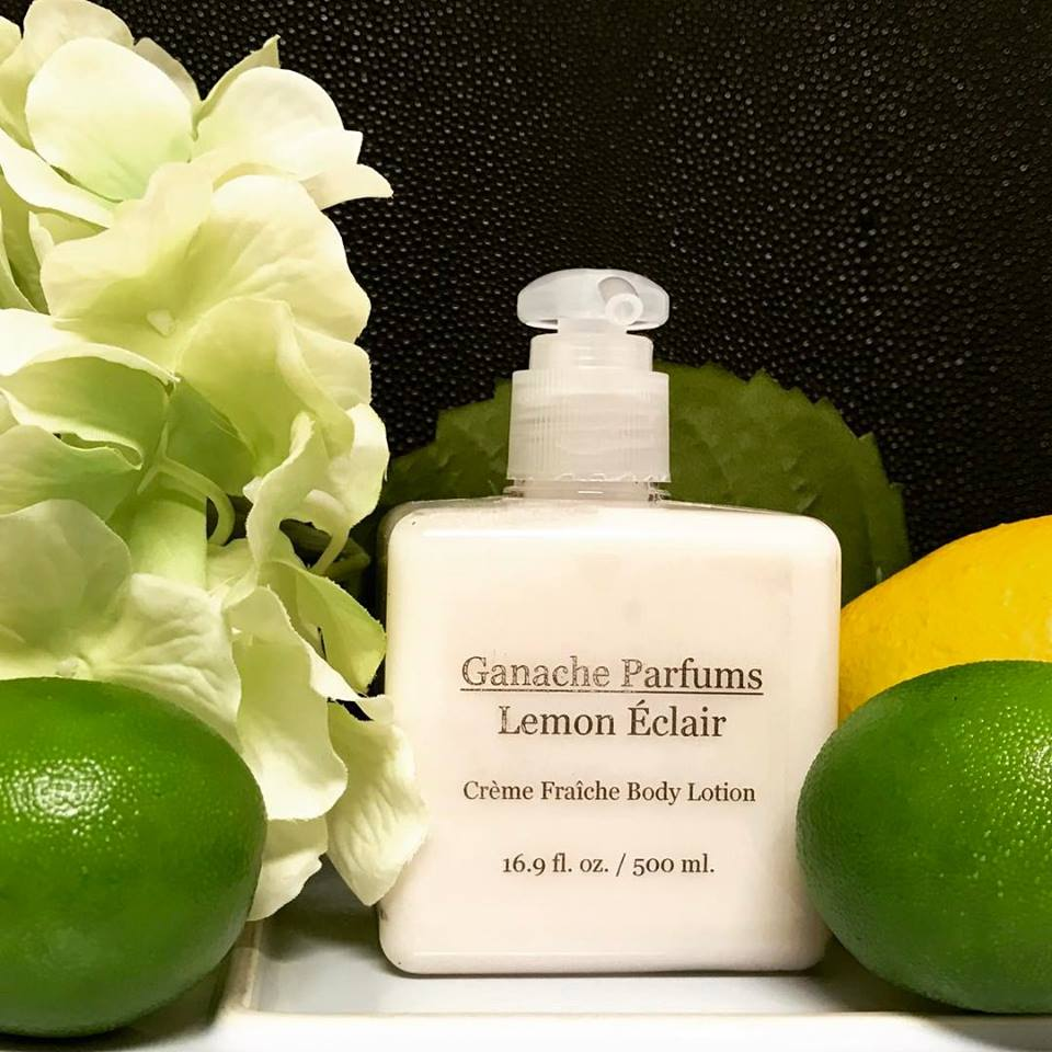 Ganache Parfums Lemon Eclair lotion next to lemons and limes and flowers