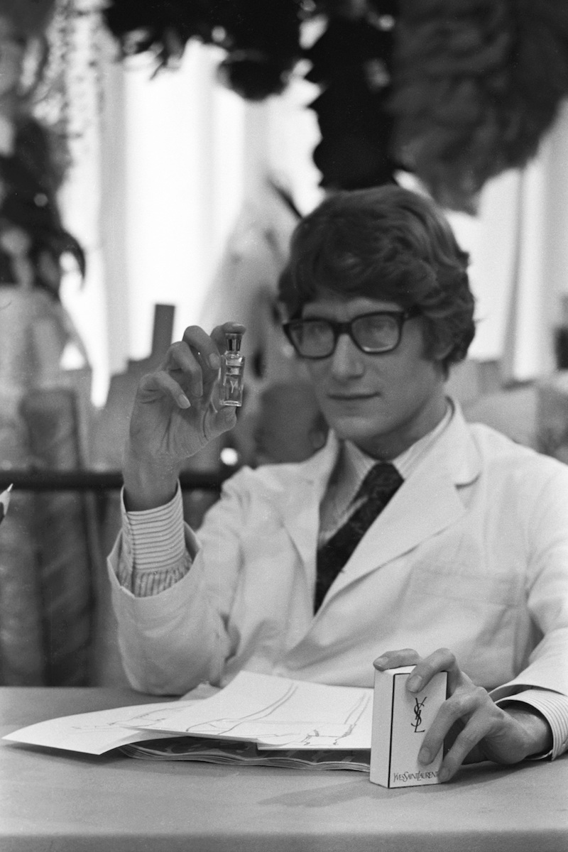 Yves Saint Laurent holding a bottle of the fragrance Y, 30 bis rue Spontini, Paris, 1966. Photograph by Giancarlo Botti.